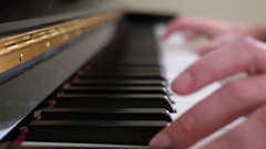 A man playing the keys on a black upright piano Stock Footage