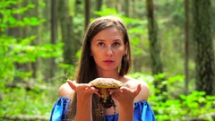 A woman in a blue dress found a big mushroom among wild forest. mystical mood Stock Footage