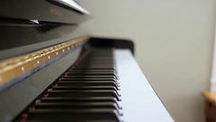A man plays the keys on a black upright piano Stock Footage