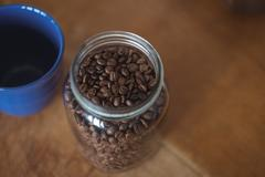 Jar of roasted coffee beans and coffee cup Stock Photos
