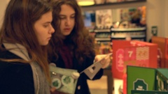 Two beautiful women choosing a New Year gift in a cosmetics shop Stock Footage