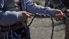 Female Rock Climber Ties Climbing Knot To Harness, Belay Partner Waits For Her Stock Footage