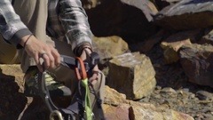 Young Man Slips Into His Rock Climbing Harness, Then Jumps Down From Boulder Stock Footage