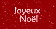 """Merry Christmas text in French """"Joyeux Noel"""" turns to dust from bottom on red Stock Footage"""