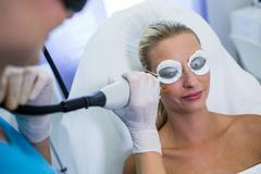 Woman receiving laser epilation treatment on her face Stock Photos