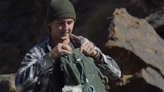 Young Man Pulls Out Rock Climbing Harness From Bag, Talks To Climbing Partner Stock Footage