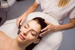 Dermatologist performing laser hair removal on patient Stock Photos