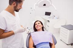 Dentist with smiling female patient Stock Photos