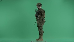 Armed serviceman standing and rounding at green screen Stock Footage