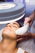Man getting a facial massage at clinic Stock Photos