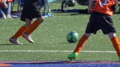 Details of a ball and boys legs playing youth soccer football on a turf field, s Stock Footage
