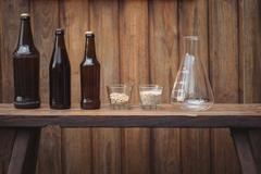 Homemade beer bottles and ingredients with a conical flask Stock Photos