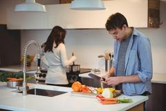 Man chopping vegetables in kitchen while woman cooking food in background Stock Photos