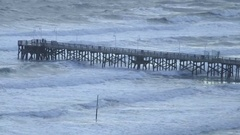 People on fishing pier watching the waves and wind blow Stock Footage
