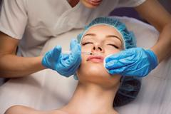 Female patient receiving an injection on her face Stock Photos