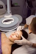 Dermatologist examining female patient skin Stock Photos