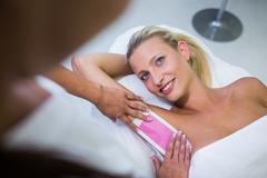 Woman getting her armpit hair removed Stock Photos