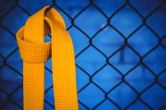 Karate yellow belt hanging on wire mesh fence Stock Photos