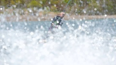 A man wakeboards behind a boat while wearing a wetsuit. Stock Footage