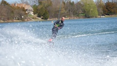 A man wakeboards behind a boat while wearing a wetsuit, slow motion. Stock Footage