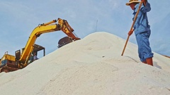 Excavator Operates on Salt Heap Man Smoothes out Salt Stock Footage