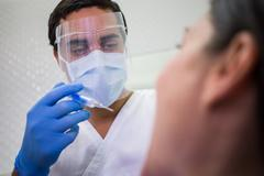 Dentist giving injection to the female patient Stock Photos