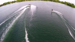 Aerial birds-eye drone view of a man wakeboarding behind a boat , slow motion. Stock Footage