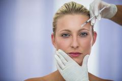 Female patient receiving a botox injection on forehead Stock Photos