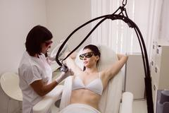Doctor performing laser hair removal on female patient skin Stock Photos