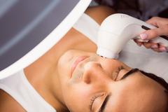 Doctor performing laser hair removal on patient face Stock Photos