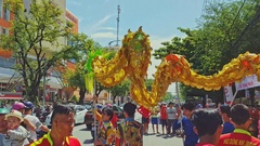 Guys Dance with Dragon on Road by Sidewalk in City with Traffic Stock Footage