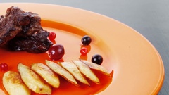 Beef meat with berries fried potatoes and cherry under sweet sauce Stock Footage