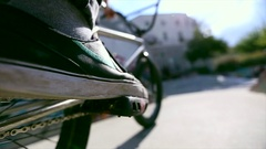 A selective-focus view of a young man riding a BMX bicycle in a concrete skate p Stock Footage