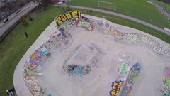 An aerial drone view of a young man riding a BMX bicycle in a concrete skate par Stock Footage