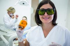 Dentist holding a dental curing ultraviolet light Stock Photos