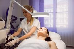 Dermatologist performing laser hair removal on patient face Stock Photos