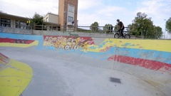 A POV of a young man riding a BMX bicycle in a concrete skate park. Stock Footage