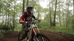 A man pushes his mountain bike while riding in a forest, slow motion. Stock Footage