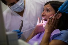 Female patient scared during a dental check-up Stock Photos