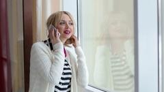 Beautiful girl talking on the phone standing near the window. Stock Footage