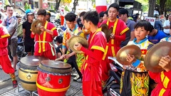 Schoolboys in Red Play Drums and Cymbals in Street Vietnam Stock Footage