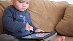 An adorable boy toddler playing with his ipad on the couch Stock Footage