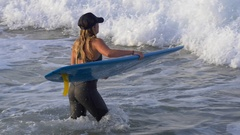A young woman in a wetsuit paddling on her longboard surfboard. Stock Footage