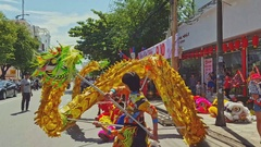 Guys Dance with Dragon on Sidewalk at Shopfront by City Street Stock Footage