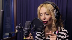 Young girl singing into a microphone in a studio. Stock Footage