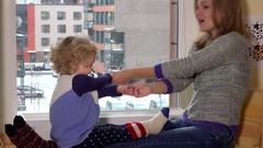 Happy woman nanny playing with toddler girl sitting near window. Snow fall Stock Footage
