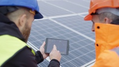 4K Technicians with tablet checking the panels at solar energy installation Stock Footage