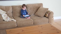 Cute little boy toddler playing on a ipad on the couch Stock Footage