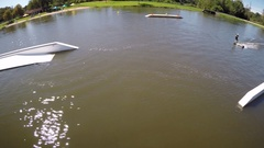 Aerial drone shot of a man riding his wakeboard at a cable park, slow motion. Stock Footage