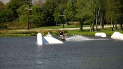 A man rides his wakeboard at a cable park, slow motion. Stock Footage